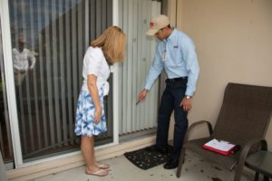 Apex Pest Control technician standing on porch with homeowner