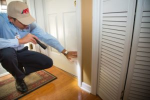 Apex Pest Control technician looking at doorway opening in home