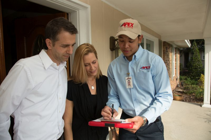 Apex Pest technician holding clipboard and talking with customers