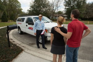 Apex Pest Control technician greeting family in driveway