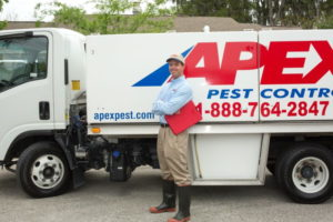 Apex Pest Control technician standing in front of truck