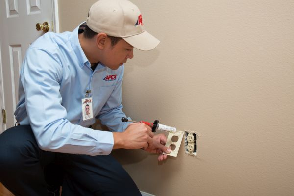 Apex Pest Control technician working on electrical outlet