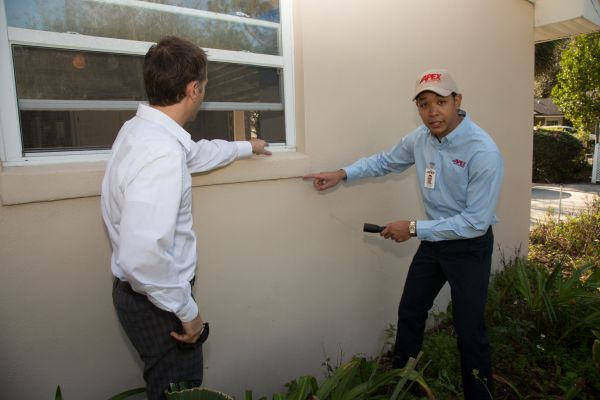 Apex Pest Control technician speaking with homeowner outside of window